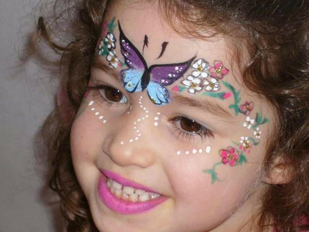 صورة عدة رسومات على وجه الطفلة مثل فراشة جميلة وزهور وألوان رائعة