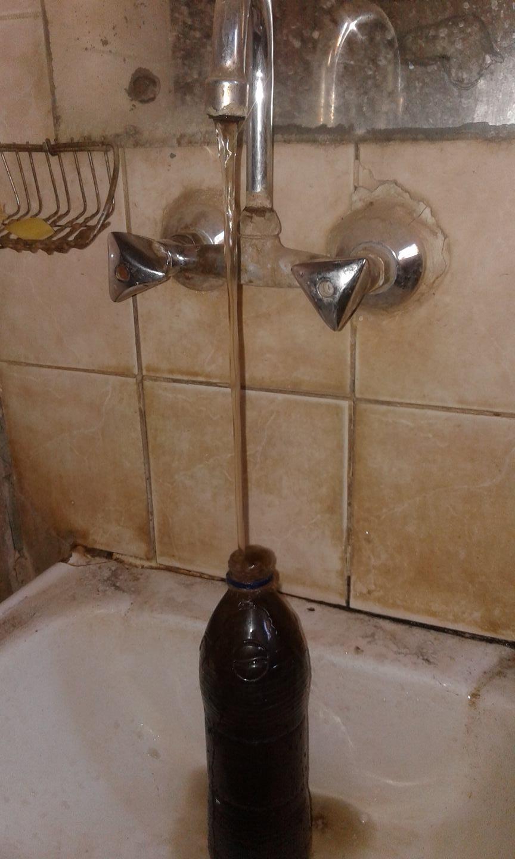 مواطن يعئى مياه الحنفية السوداء بالزجاجة