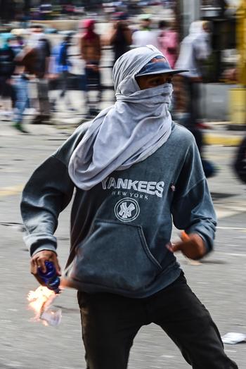 أحد المتظاهرين يحمل زجاجة حارقة