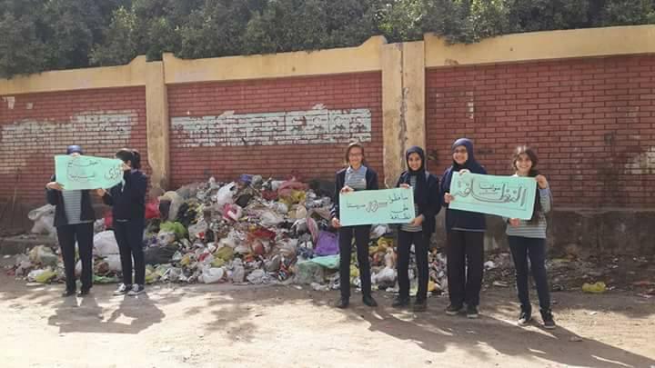 1-طلاب مدرسة يرفعون لافتات لرفع القمامة
