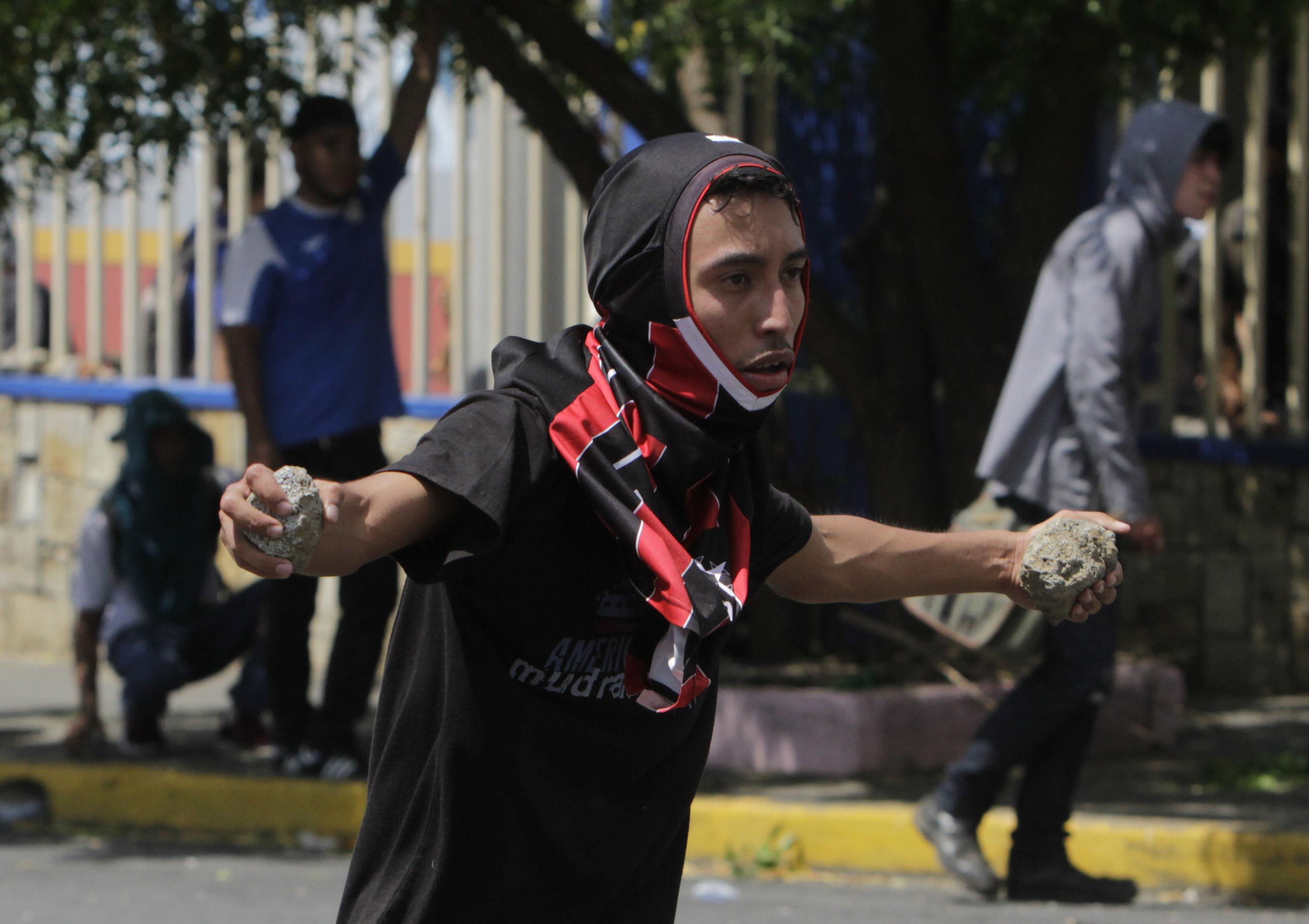 طالب فى يده الحجارة خلال الاشتباك مع قوات الأمن