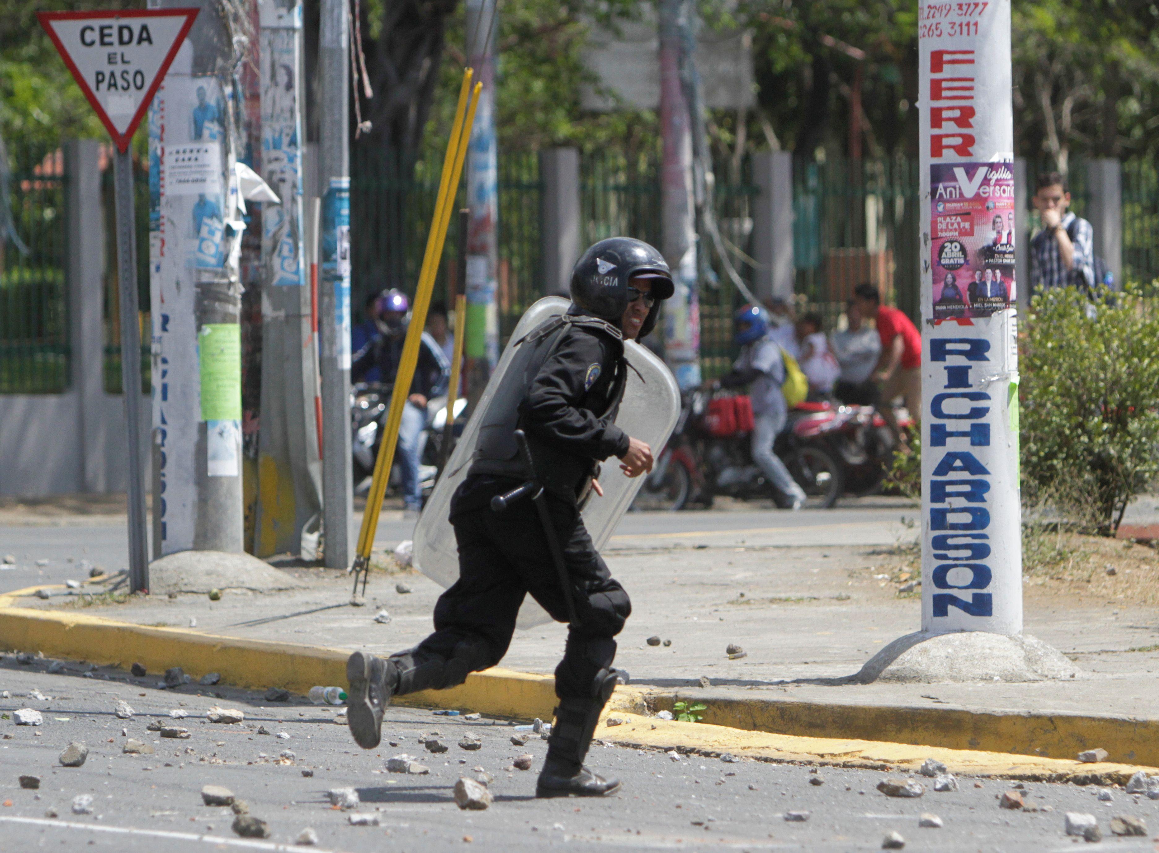 أحد عناصر الشرطة يجرى من حجارة المتظاهرين