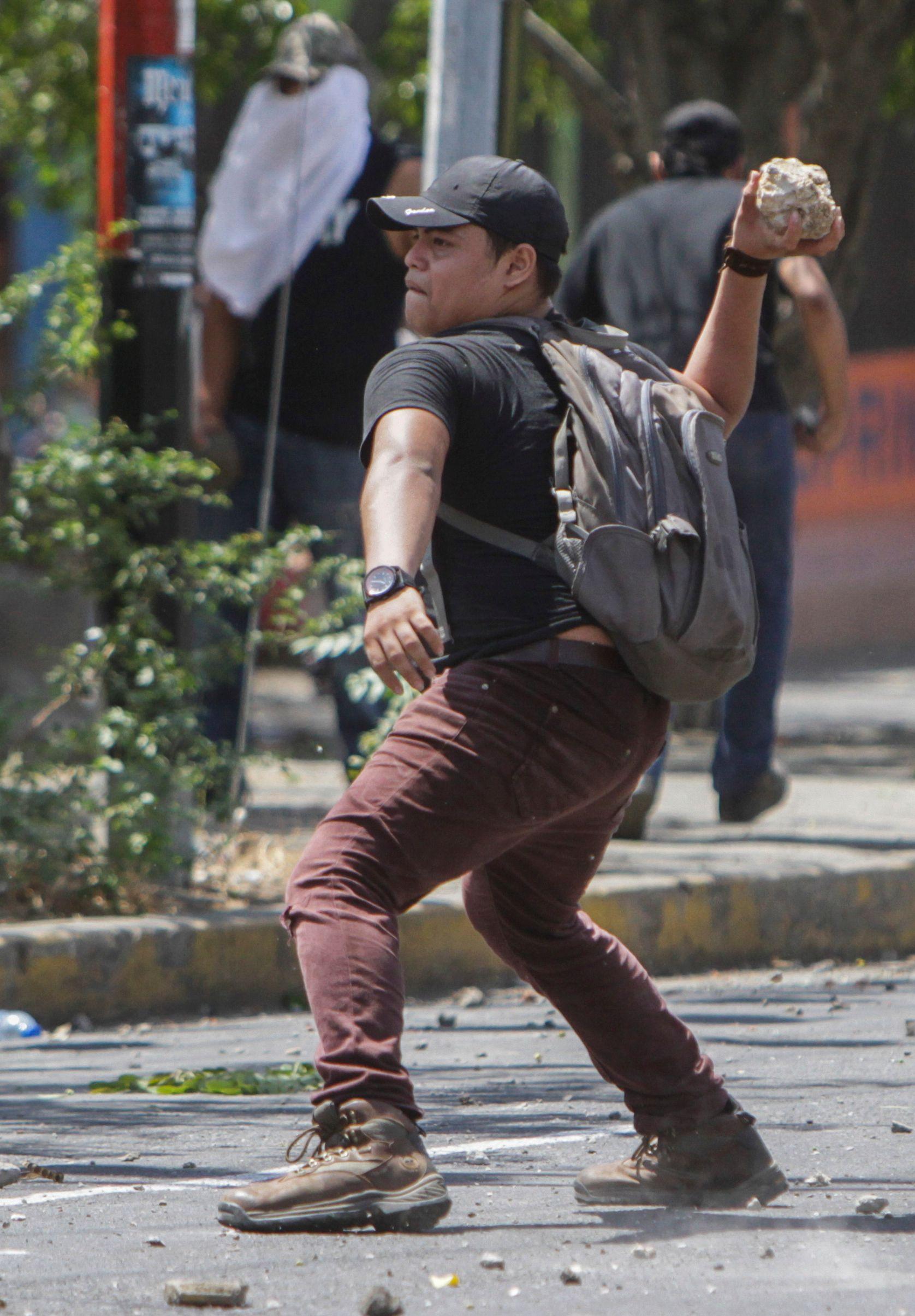 أحد الطلاب يشتبك مع الشرطة بالحجارة