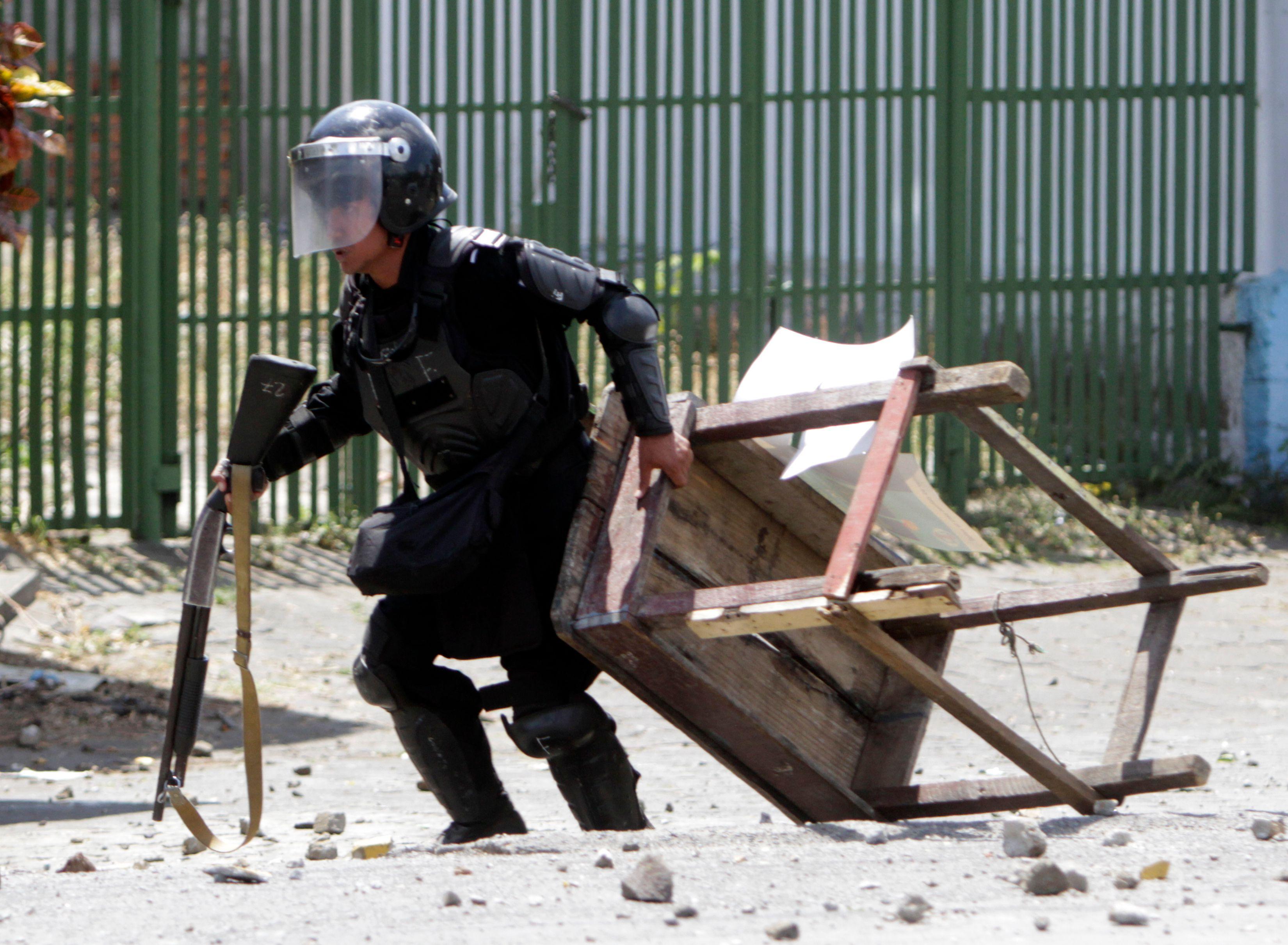 أحد عناصر الشرطة يحتمى من حجارة المتظاهرين