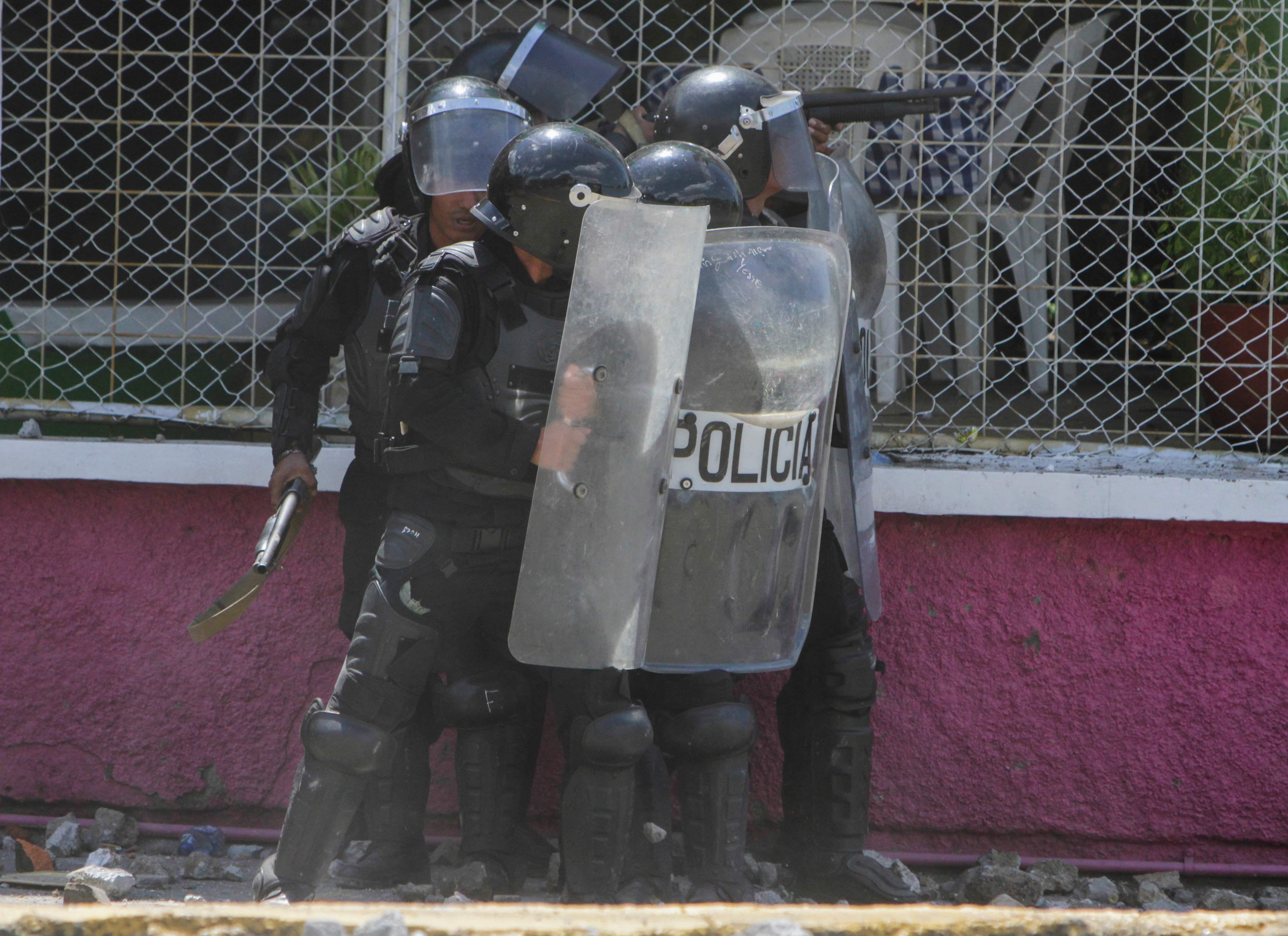 الشرطة تحتمى خلف الدروع من حجارة المتظاهرين