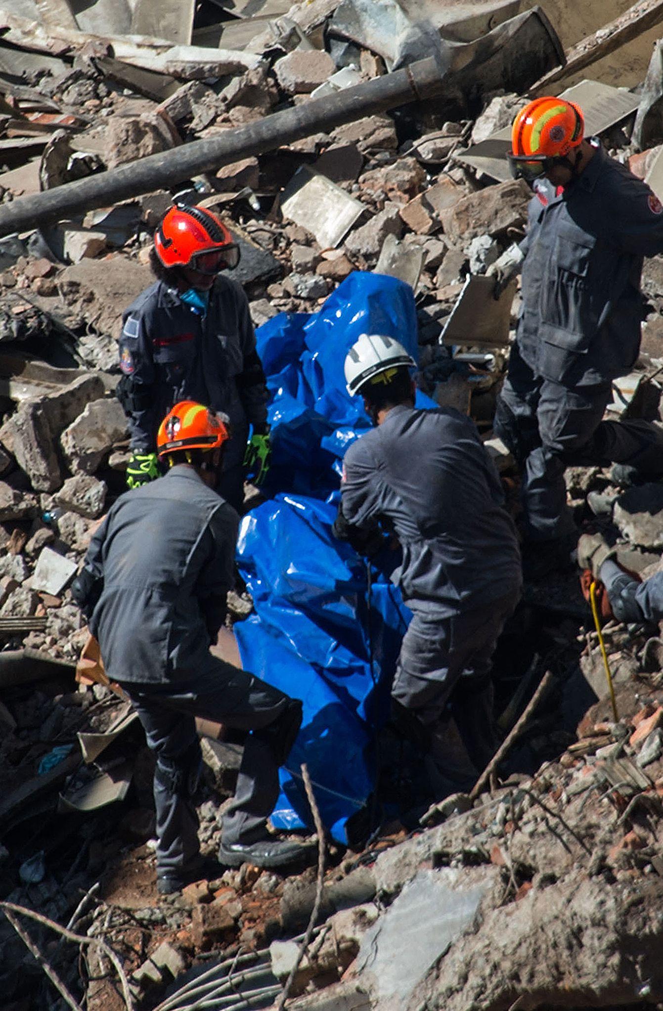 عمال الانقاذ يبحثون عن مفقودين أسفل عقار منهار