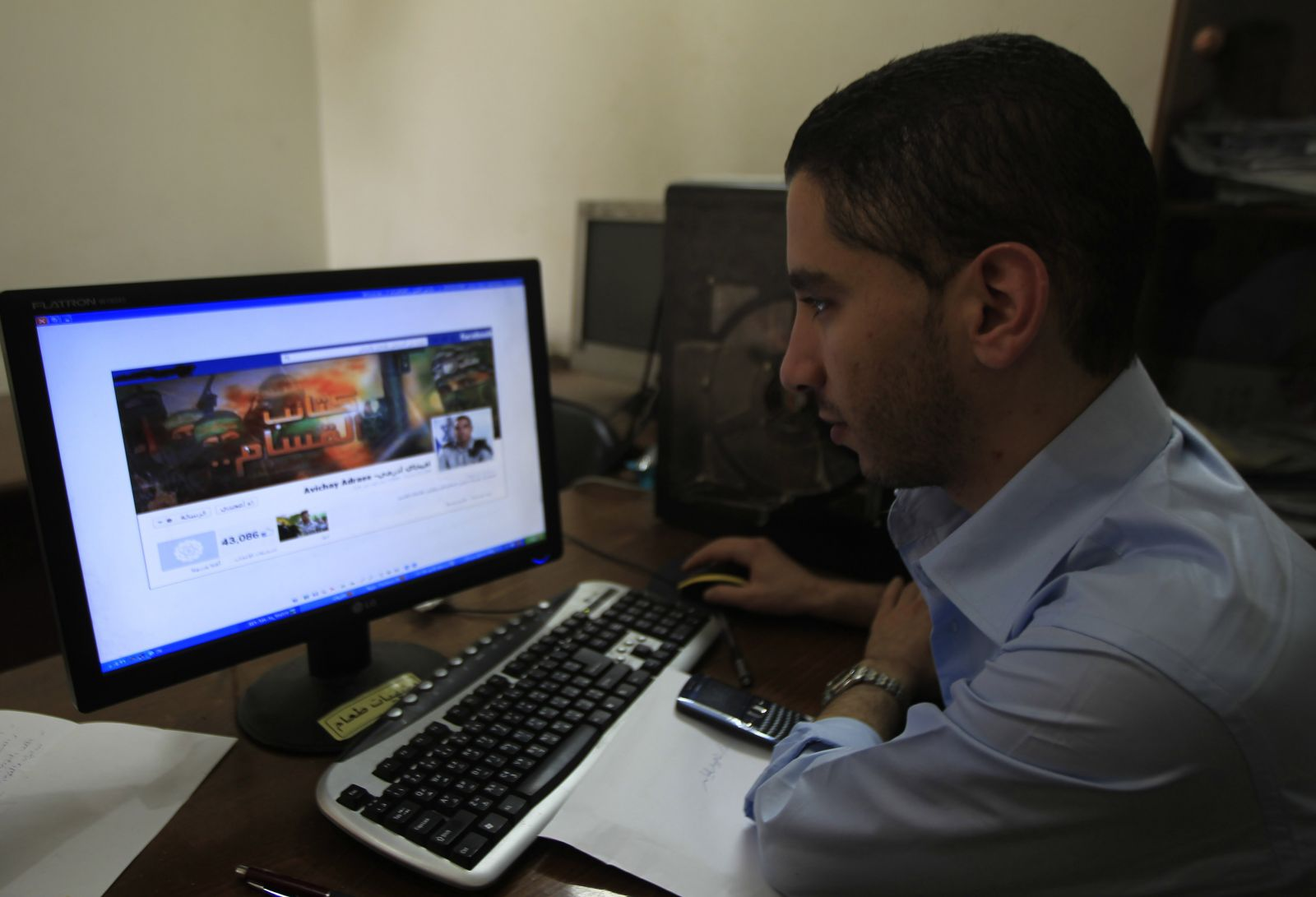A-Palestinian-man-looks-at-the-Facebook-page-of-Avichay-Adraee-the-spokesman-of-the-Israeli-Army-to-the-Arabic-media