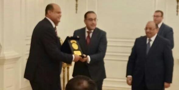 علاء أبو زيد محافظ مرسى مطروح السابق يتسلم درع التكريم من مدبولى