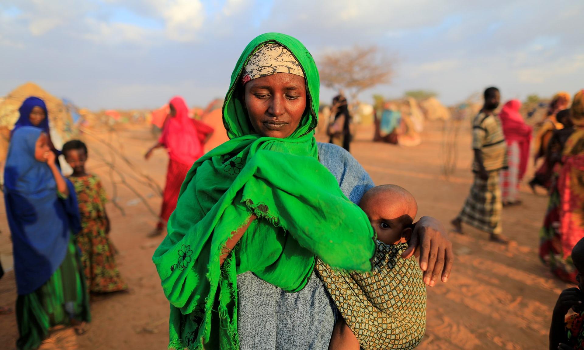 إمرأة صومالية تحمل طفلها