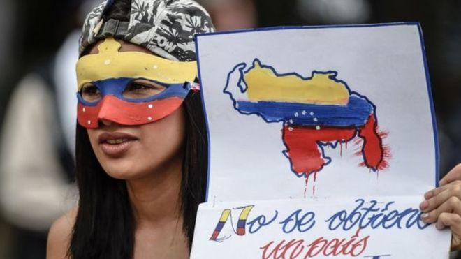 فتاة فنزويلية ترتدي قناع خلال مشاركتها بالاحتجاجات