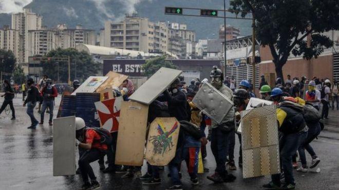 متظاهرين يحملون حواجز للإحتمال من رصاصات الشرطة
