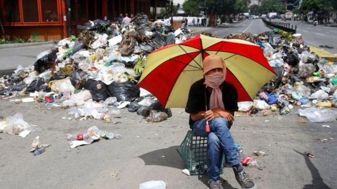 متظاهر ملثم يجلس بجوار كوم من القمامة