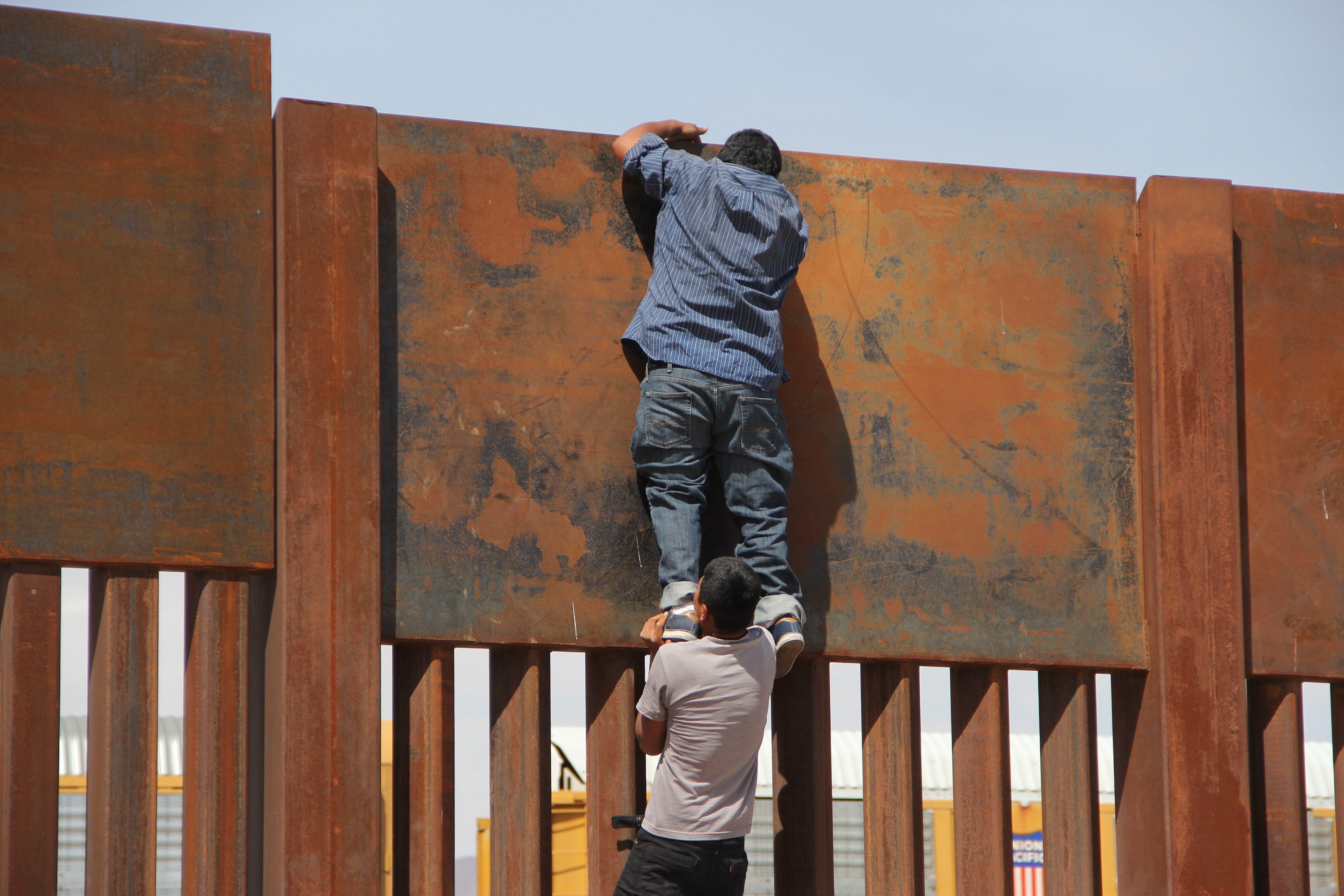أحد المهاجرين يجتاز الجدار الحدودى بين الولايات المتحدة والمكسيك