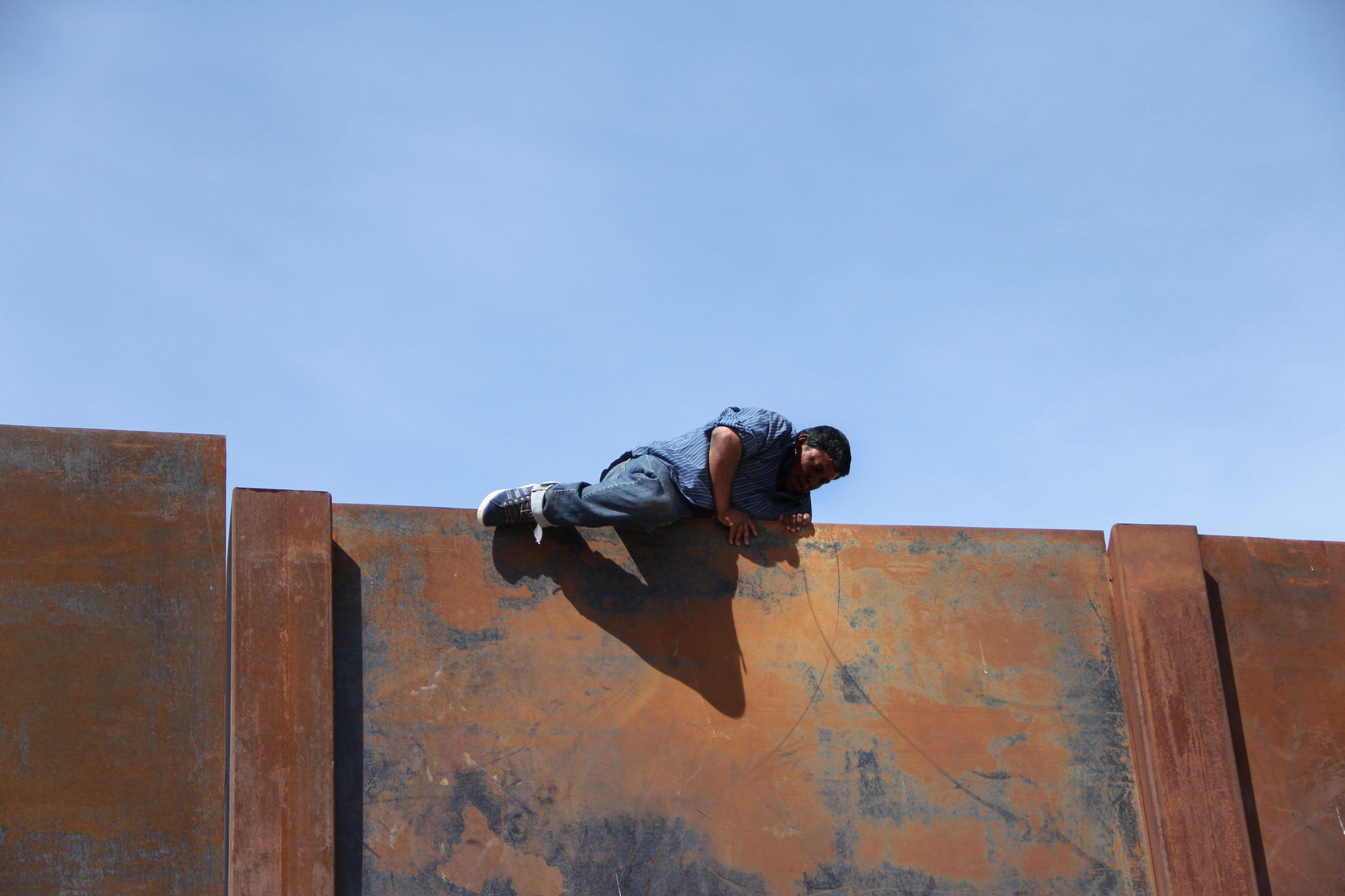 أحد المهاجرين فوق الجدار الحدودى