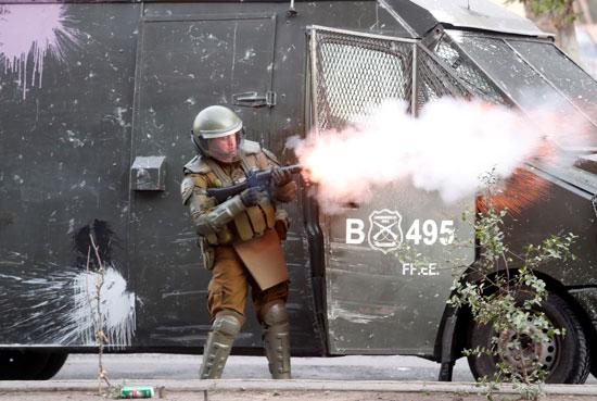 شرطى يطلق قذائف غاز على المتظاهرين