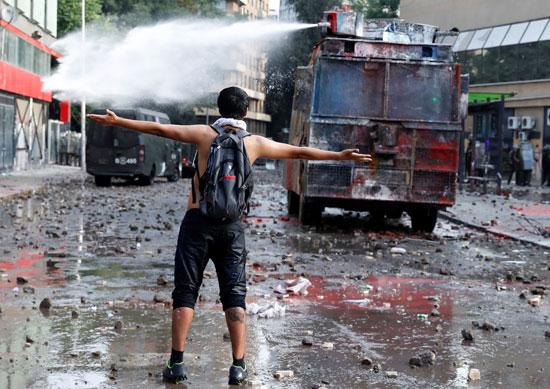 متظاهر يستعرض شجاعته أمام رشاشات المياه