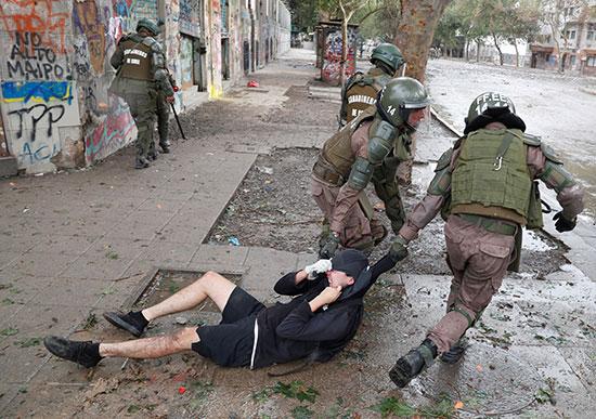الشرطة تسحب متظاهر على الأرض