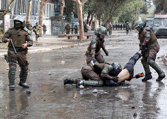 الشرطة تسحل أحد المتظاهرين فى تشيلى