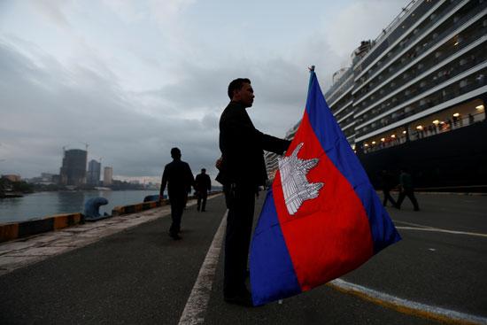 راكب بالسفينة يلوح بالعلم الكمبودى امتنانا لقبول السلطات استقبالهم