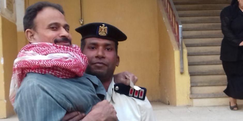 أمين شرطة بسوهاج يحمل مريضا للجنته بالطابق الثالث للمشاركة بالاستفتاء (صور)