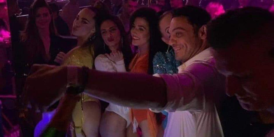 المقاول الهارب محمد علي يتفاخر بين أصدقائه بسهراته الحمراء وسط أحضان فتيات الليل بأسبانيا