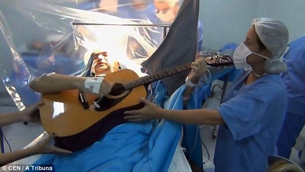 مريض يعزف أثناء جراحة إزالة ورم بالمخ علي الجيتار للاطمئنان علي سير العملية