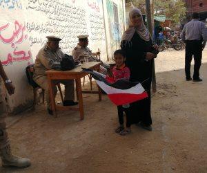 ربة منزل تصطحب طفلتها وبيدها علم مصر أثناء الاستفتاء: لتعليمها الانتماء